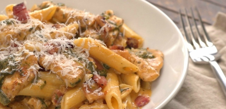Close-up of creamy penne with bacon and Parmesan with fork
