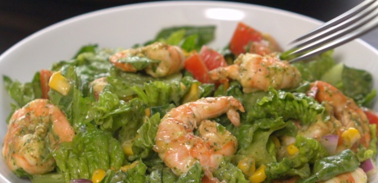 Close-up of fork piercing shrimp avocado salad
