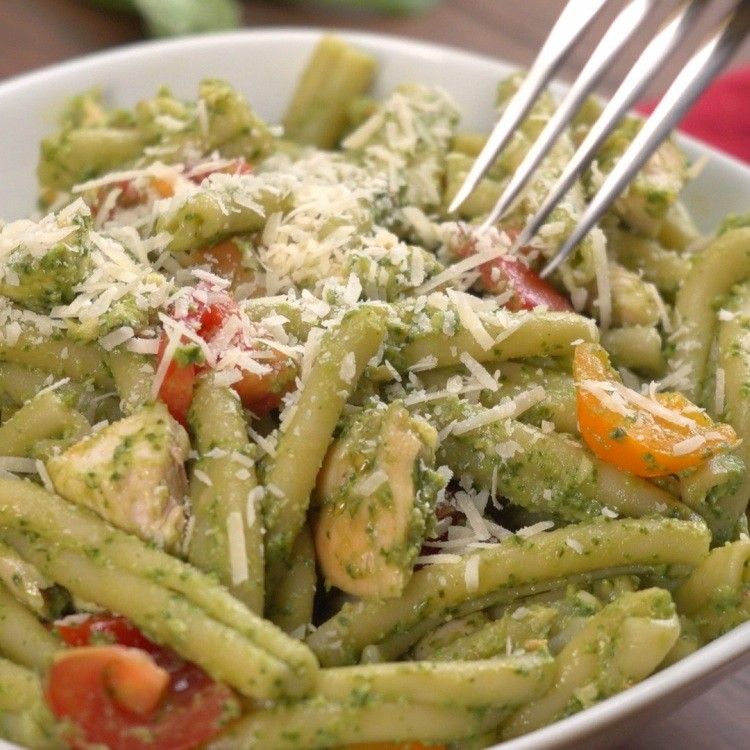 Eating pasta mixed with pesto sauce of avocado and garlic