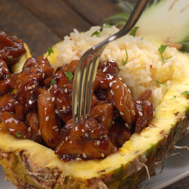 Fork getting teriyaki chicken out of pineapple boat