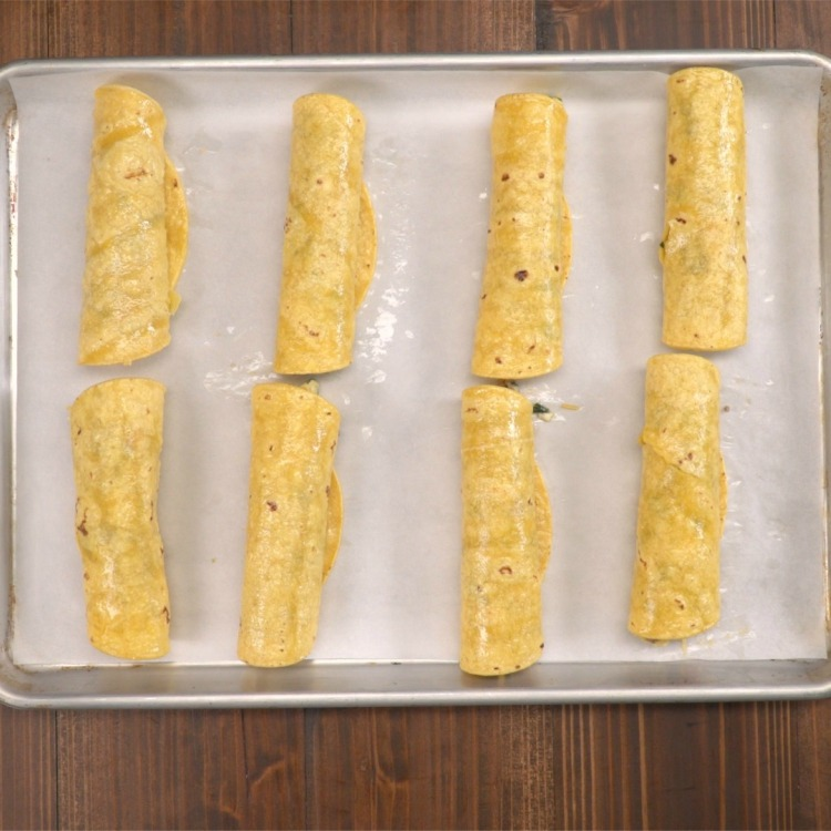 Rolled breakfast taquitos on sheet pan to bake