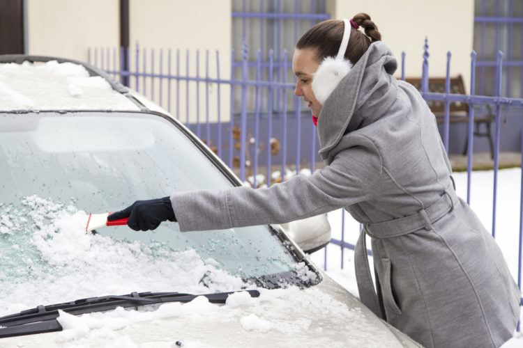 Woman cleans snows off her car.
