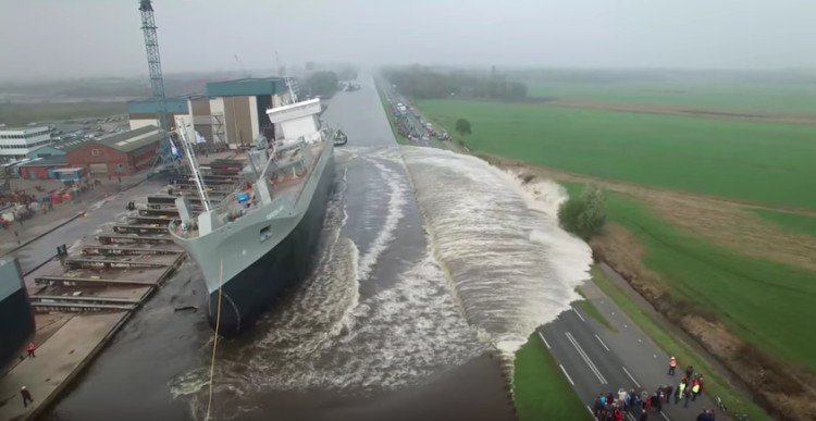 Giant ship goes from land to water.