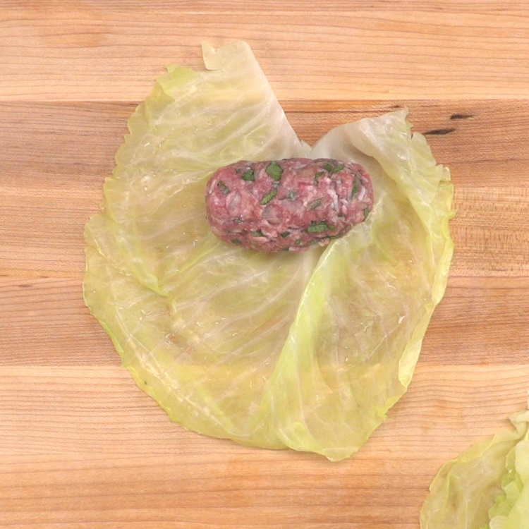Place meat horizontally on the cabbage leaf near the base