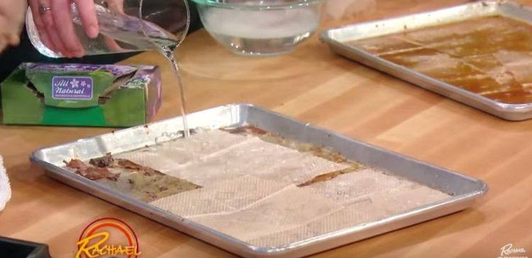 Image of water being poured on dirty baking sheet.