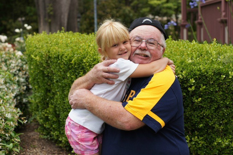 Image of grandfather hugging child.