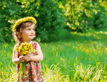Image of toddler girl with floral head wreath on and flowers bunch in hands.