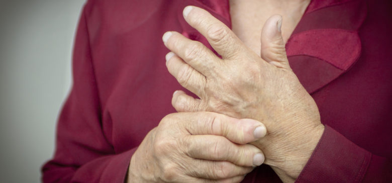 Image of woman holding hand in pain.