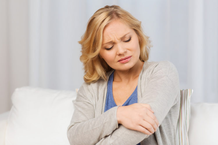 Image of woman holding arm in pain