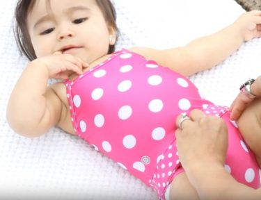 Image of baby in a pink polka-dotted bathing suit