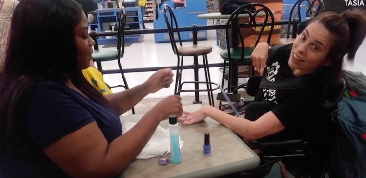Image of Walmart employee painting woman with cerebral palsy's nails