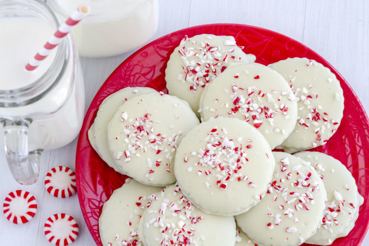 Image of Fresh baked chocolate peppermint cookies coated with white chocolate and candy cane sprinkles stacked on a festive red plate with 2 glasses of milk
